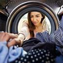 A woman grabbing laundry from a machine
